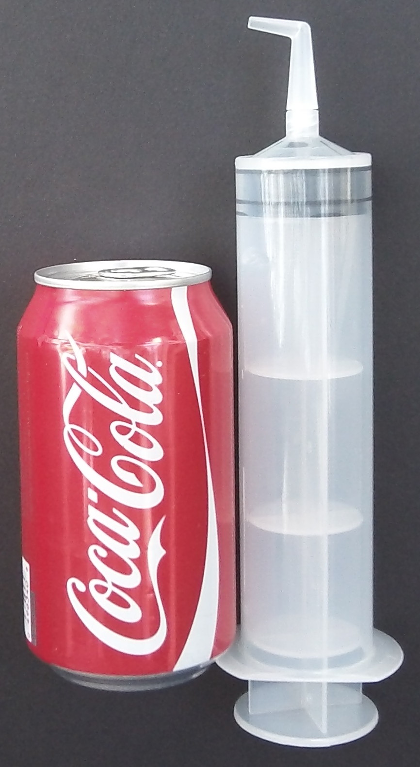 Size comparison of ear syringe to soda can.